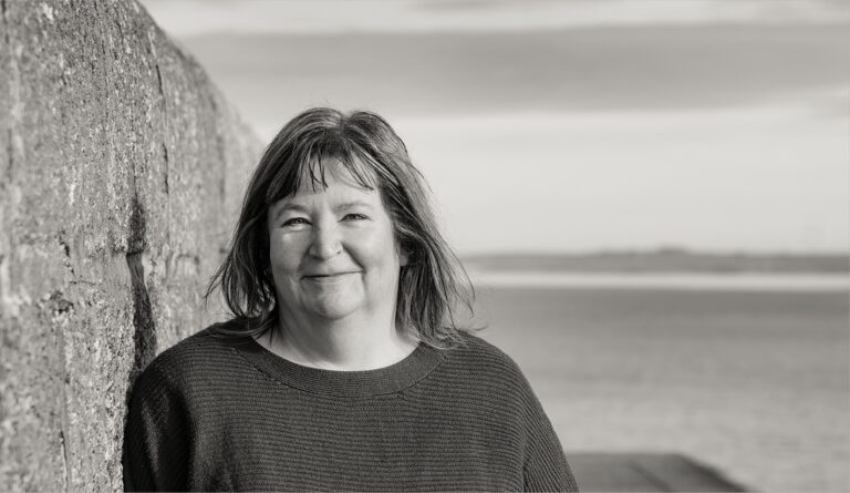 Anne standing by harbour wall